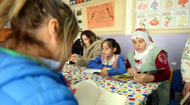 Köylüler sınıfta çocuklarıyla kitap okuyor