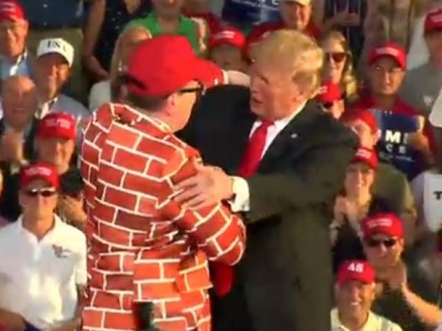 Trump duvar desenli takım elbise giyinmiş destekçisini sahneye çağırdı
