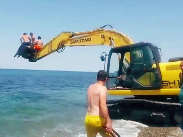 İş makinesi ile gençlerin deniz eğlencesine ortak oldu