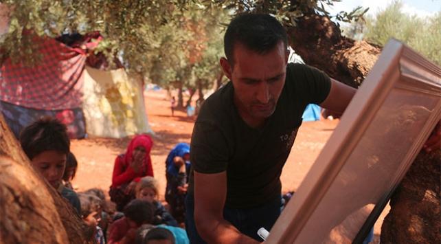 Savaş mağduru çocuklara ağaç altında eğitim veriyor