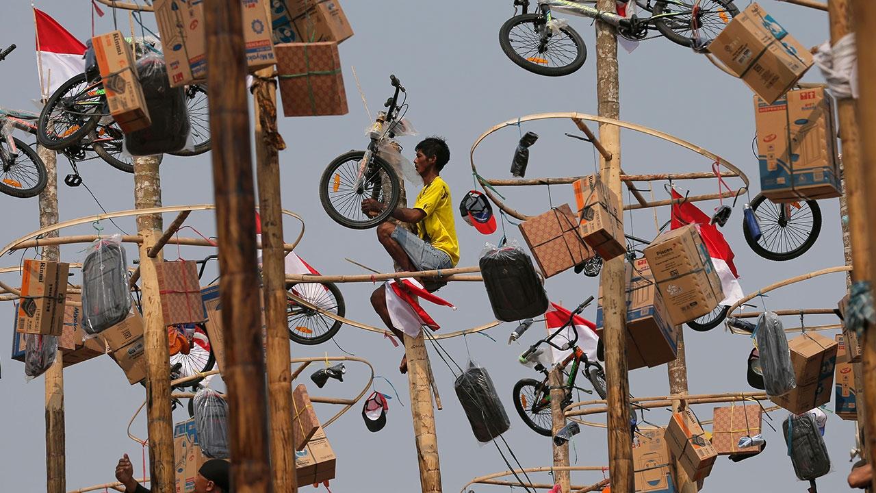 Endonezyalılar ödül için yağlı direğe tırmandı