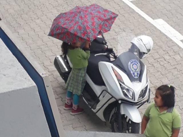 Kırık şemsiyesi ile polis motosikletini yağmurdan korudu