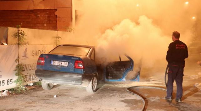Park halindeki otomobili yanarken bagajdaki malzemeleri kurtarmaya çalıştı