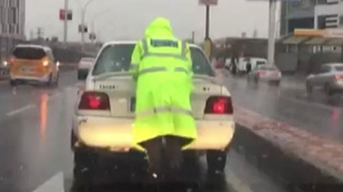 Arızalanan otomobilin yağmur altında polis tarafından itilme anı kameraya yansıdı