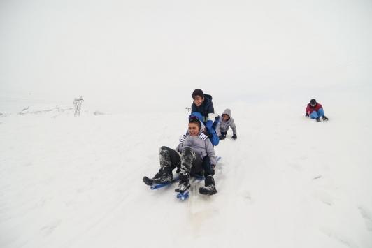 Tuncelide çocukların karlı tepelerde kızak keyfi