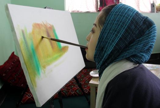 Ağzıyla çizdiği resimleri satarak ailesinin geçimini sağlıyor
