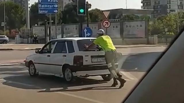Yolda kalan sürücünün aracını trafik polisi iterek yardım etti