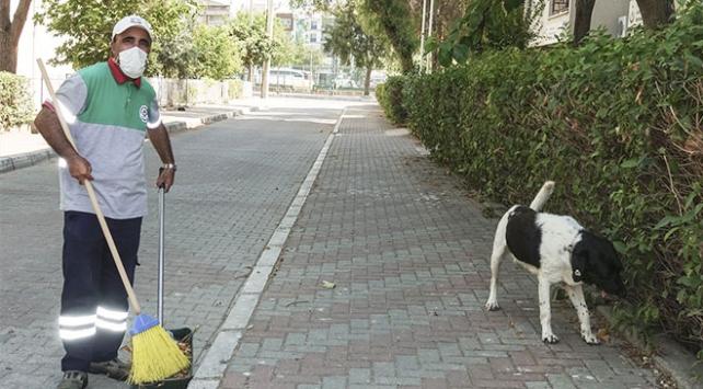 Üç bacaklı sokak köpeği ile temizlik işçisinin dostluğu