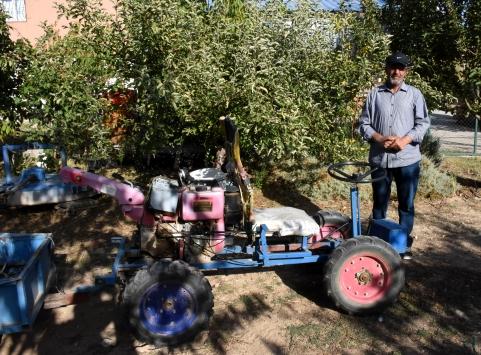 Hurda malzemelerden yaptığı tarım aletleriyle ceviz bahçesinin bakımını yapıyor