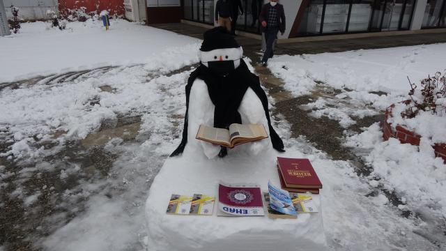Vanlı gençler maske taktıkları kardan adamın etrafında kitap okudu