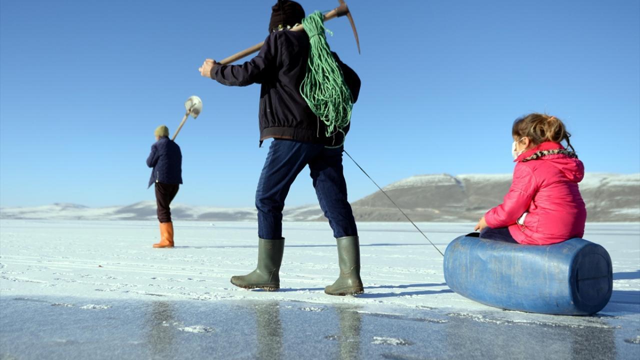 Erken saatlerde hazırlanan balıkçılar, buzla kaplı gölde yürüyerek ağlarını bırakacakları alana geliyor.