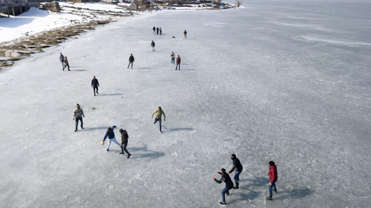 Köylü gençlerin donan göl üzerinde futbol keyfi