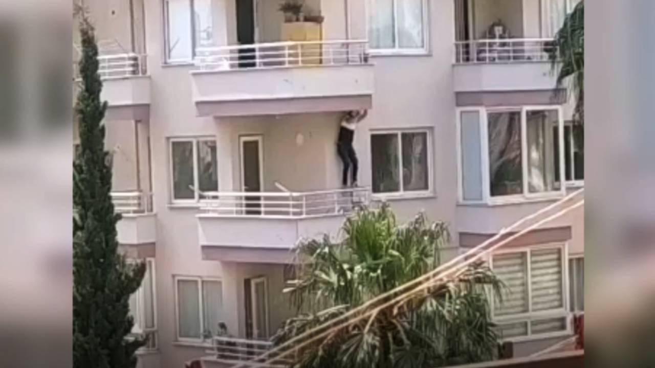 Polisi görünce balkondan balkona sarktı