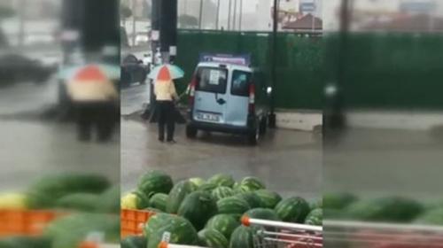 Sağanak yağmur altında araba temizledi