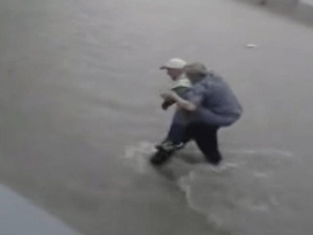 Trafik polisi selde mahsur kalan vatandaşı sırtında taşıdı