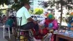 Palyaço kostümüyle hem ayakkabı boyuyor hem insanları eğlendiriyor
