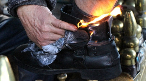 Müşterilerin ayakkabılarını ateşle yakarak boyuyor